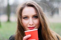 Портрет кофе молодой красивой стильной девушки выпивая в парке Стоковая Фотография
