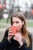 Портрет кофе молодой красивой стильной девушки выпивая в парке Стоковые Изображения RF