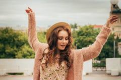 портрет красивая девушка в шляпе, девушка танцует в городе Руки поднятые вверх красный цвет девушки с волосами стоковая фотография