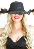 Портрет Красивая молодая блондинка в черной шляпе с neckline на белой предпосылке красиво усмехаясь стоковая фотография