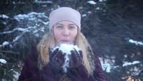 Портрет Красивая счастливая девушка дует снег от ее рук на открытом воздухе в зиме имея хорошую озлобленность видеоматериал