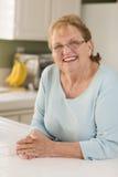 Портрет красивейшей старшей взрослой женщины в кухне Стоковые Изображения RF