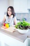 Молодая женщина стоя на счетчике кухни Стоковое Изображение RF