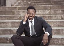 Портрет красивого Афро-американского бизнесмена говоря на мобильном сидя outdoors на лестницах города стоковая фотография
