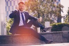 Портрет красивого бизнесмена говоря на мобильном телефоне пока имеющ закуски Стоковая Фотография RF
