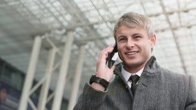 Портрет красивого бизнесмена используя смартфон и выпивать стоковое фото