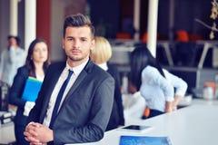 Портрет красивого бизнесмена перед его командой стоковая фотография