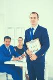 Портрет красивого бизнесмена стоя в офисе с коллегами Стоковые Фото