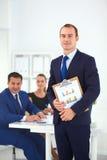 Портрет красивого бизнесмена стоя в офисе с коллегами Стоковая Фотография