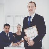 Портрет красивого бизнесмена стоя в офисе с коллегами Стоковое Изображение RF