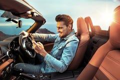 Портрет красивого, богатый человек управляя его обратимым автомобилем Стоковое фото RF