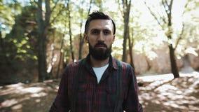 Портрет красивого бородатого человека идя в lumberjack леса a смотря в камеру сток-видео