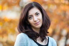 Портрет красивого брюнет на предпосылке листвы Стоковая Фотография