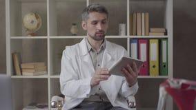 Портрет красивого внимательного человека в белой робе смотря в планшете показа камеры с изображением рентгеновского снимка легких акции видеоматериалы