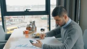 Портрет красивого вычисления бизнесмена на его smartphone и проверять бумажные диаграммы в кафе сток-видео