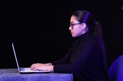 Портрет красивого и умного хакера девушки с компьтер-книжкой на темной предпосылке используя стекла пока она работает Стоковые Фотографии RF