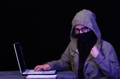 Портрет красивого и умного хакера девушки с компьтер-книжкой на темной предпосылке используя стекла и покрывать ее шею, рот Стоковые Фотографии RF
