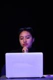 Портрет красивого и умного хакера девушки с компьтер-книжкой на темной предпосылке используя стекла в ее голове пока она Стоковые Изображения RF
