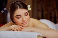 Портрет красивого конца-вверх женщины лежа вниз в салоне курорта Стоковые Фото