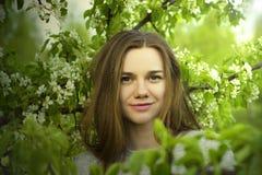 Портрет красивого конца маленькой девочки вверх среди blossoming дерева с зеленым цветом выходит outdoors Стоковые Фотографии RF