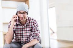 Портрет красивого модного бородатого бизнесмена или архитектор звоня со смартфоном из современного офиса стоковые изображения rf