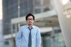 Портрет красивого молодого азиатского бизнесмена стоя, что и смотря препровождать на запачканной городской предпосылке города зда Стоковые Изображения RF