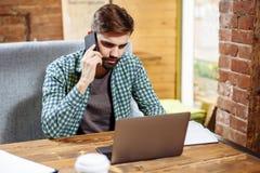 Портрет красивого молодого бизнесмена сидя на столе с компьтер-книжкой и говоря на мобильном телефоне черный телефон приемника пр Стоковое фото RF