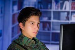 Портрет красивого молодого солдата нося военную форму, воинский оператора трутня наблюдая на его компьютере Стоковое Изображение
