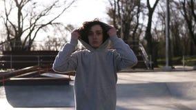Портрет красивого молодого человека с темным вьющиеся волосы Предназначенный для подростков мальчик в hoodie идя над парком коньк видеоматериал