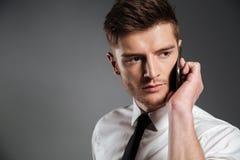 Портрет красивого молодого бизнесмена говоря на мобильном телефоне Стоковая Фотография