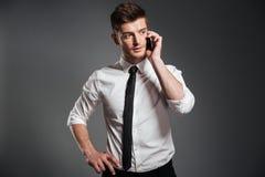 Портрет красивого молодого бизнесмена говоря на мобильном телефоне Стоковое Изображение