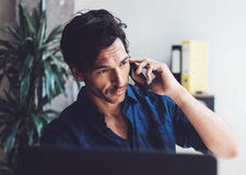 Портрет красивого молодого бизнесмена работая на солнечном месте работы на компьтер-книжке Усмехаясь человек делая мобильный теле Стоковые Изображения RF