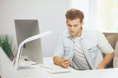Портрет красивого молодого бизнесмена сидя на таблице офиса с персональным компьютером и писать на мобильном телефоне Стоковая Фотография RF