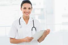 Портрет красивого молодого женского доктора с доской сзажимом для бумаги Стоковое Изображение RF