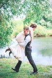 Портрет красивого молодого человека нося привлекательную женщину на его задняя часть outdoors Пары потехи Невеста и gr Стоковые Изображения