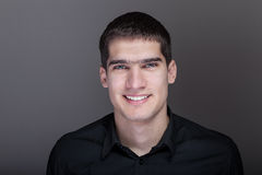 Портрет красивого молодого человека усмехаясь над серой предпосылкой Стоковое Изображение RF