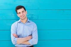 Портрет красивого молодого человека усмехаясь при пересеченные оружия стоковые фотографии rf