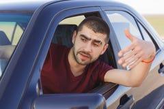 Портрет красивого мужского водителя развевает от окна автомобиля, вставляемый в заторе движения, чувствует слабонервным и потрево стоковые изображения rf