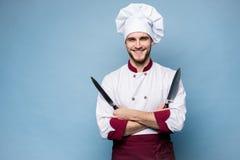 Портрет красивого мужского повара шеф-повара держа ножи изолированный на светлом - голубая предпосылка стоковые изображения rf