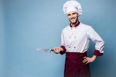 Портрет красивого мужского повара шеф-повара держа ножи изолированный на светлом - голубая предпосылка стоковое фото rf
