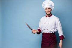 Портрет красивого мужского повара шеф-повара держа ножи изолированный на светлом - голубая предпосылка стоковые фото