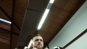 Портрет красивого мужского спортсмена, который имеет тренировку с чайниками в современном спортзале видеоматериал