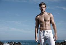 Портрет красивого, мышечного человека с бурным морем в bac Стоковые Изображения RF