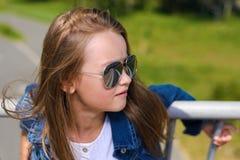 Портрет красивого платья inwhite маленькой девочки в голубых куртке и солнечных очках джинсовой ткани стоковое фото rf