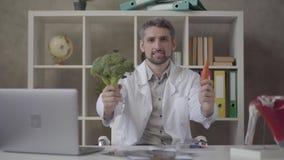 Портрет красивого положительного человека в белой робе смотря в камере предлагая морковь и брокколи Умелый доктор внутри видеоматериал