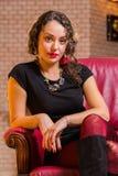Портрет красивого романтичного брюнет на красном стуле стоковое фото