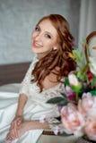 Портрет красивого рыжеволосого усаживания девушки, усмехаясь на большом кресле Стоковые Изображения