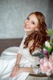 Портрет красивого рыжеволосого усаживания девушки, усмехаясь на большом кресле Стоковая Фотография