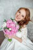 Портрет красивого рыжеволосого усаживания девушки, усмехаясь на большом кресле Стоковые Фото