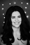Портрет красивого усмехаясь брюнет с длинными волосами весёло Фотография студии, электрические лампочки bokeh черная белизна стоковое изображение